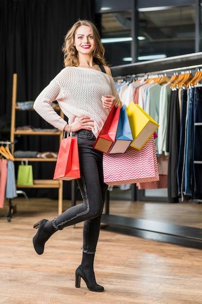 Bella donna alla moda che posa nel boutique con il sacchetto della spesa variopinto della tenuta Foto Gratuite