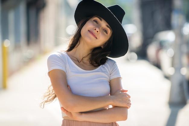 Bella donna alla moda dell'adolescente che posa con il cappello Foto Premium