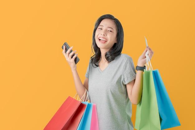 Bella donna asiatica allegra che tiene i multi sacchetti della spesa e carta di credito colorati con lo smartphone su arancione-chiaro. Foto Premium