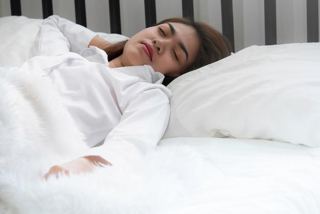 Bella donna asiatica che dorme sul letto in camera da letto Foto Premium