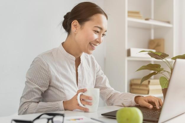 Bella donna asiatica che lavora al computer portatile Foto Gratuite