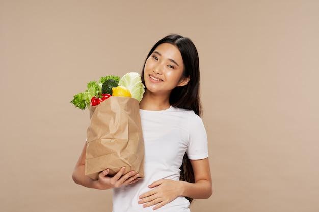 Bella donna asiatica che posa con la borsa delle verdure Foto Premium