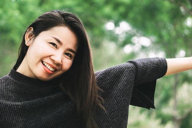 Bella donna asiatica che sorride alla macchina fotografica con la natura all'aperto Foto Premium