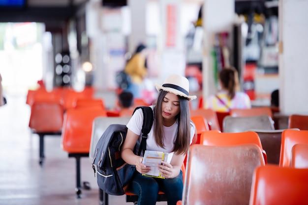 Bella donna asiatica che sorride con la mappa e borsa all'autostazione Foto Gratuite