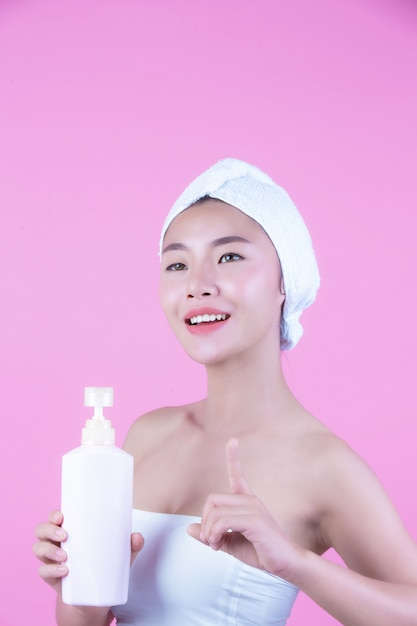 Bella donna asiatica che tiene una bottiglia di prodotto su uno sfondo rosa. Foto Gratuite