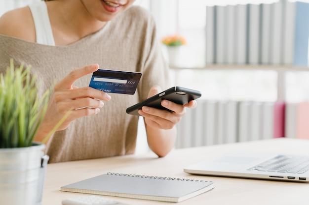 Bella donna asiatica che utilizza smartphone che compra acquisto online Foto Gratuite