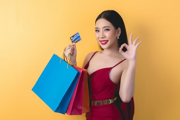 Bella donna asiatica con il sacchetto della spesa e la carta di credito a disposizione Foto Gratuite