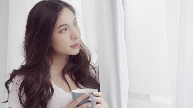 Bella donna asiatica felice che sorride e che beve una tazza di caffè o un tè vicino alla finestra nella camera da letto. Foto Gratuite