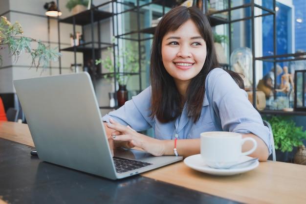 Bella donna asiatica in camicia blu facendo uso del computer portatile e bevendo caffè Foto Premium