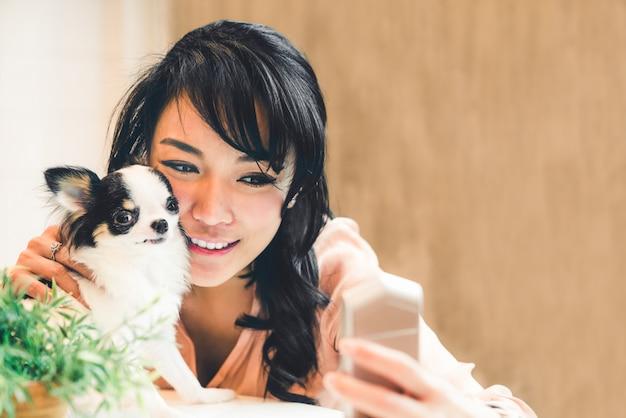Bella donna asiatica prendendo selfie con cane carino chihuahua a casa Foto Premium