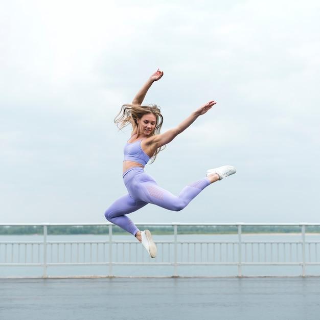 Bella donna atletica che salta possibilità remota Foto Gratuite