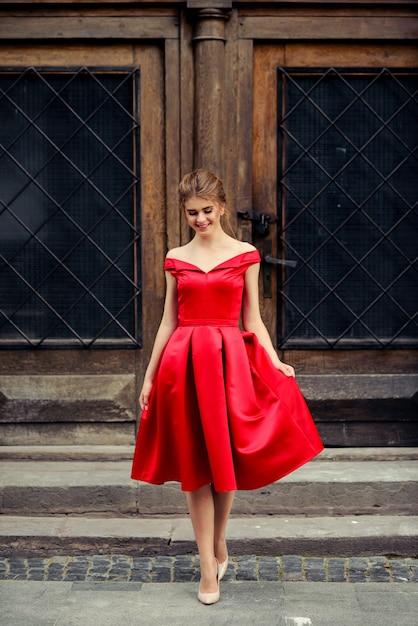 Bella donna attraente in vestito rosso nella città sopra la vecchia porta d'annata Foto Premium