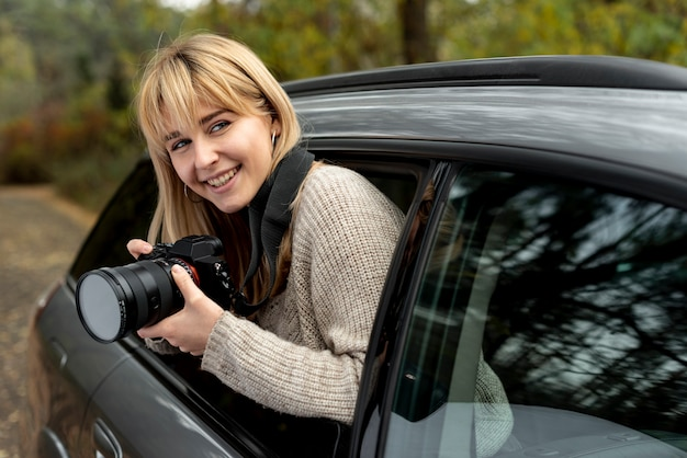 Bella donna bionda che tiene una macchina fotografica professionale Foto Gratuite