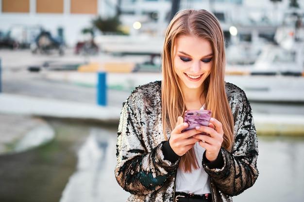 Bella donna bionda felice che cammina e che scrive i messaggi degli sms Foto Premium