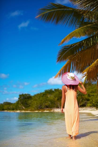 Bella donna calda in cappellino da sole variopinto e vestito che camminano vicino all'oceano della spiaggia il giorno di estate caldo vicino alla palma Foto Gratuite