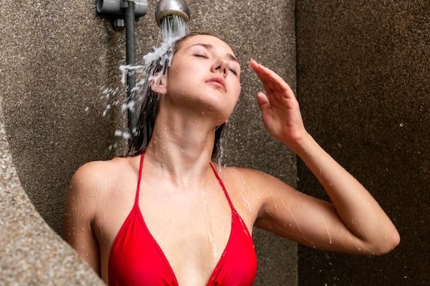 Bella donna caucasica in bikini rosso che fa la doccia fuori. Foto Premium
