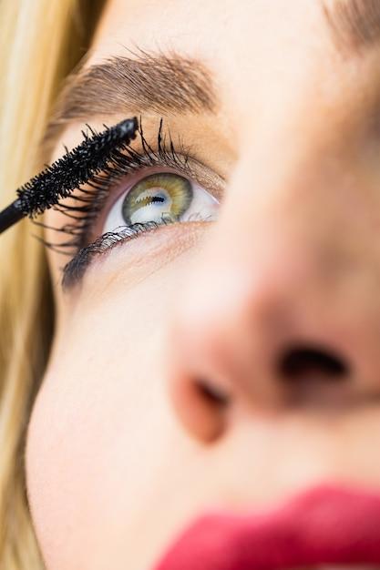 Bella donna che applica mascara sulle ciglia Foto Premium