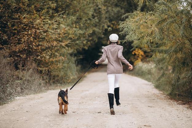 Bella donna che cammina fuori il suo cane nel parco di autunno Foto Gratuite