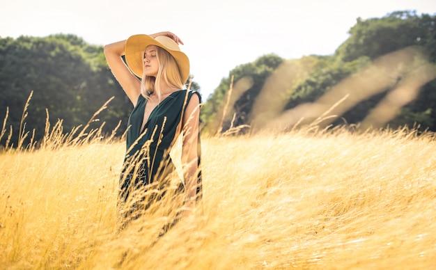 Bella donna che cammina in un campo di grano e che respira in profondità Foto Premium