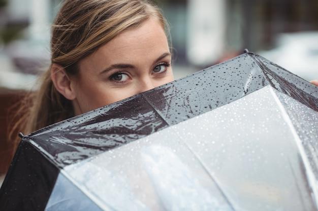 Bella donna che copre il viso con l'ombrello Foto Gratuite