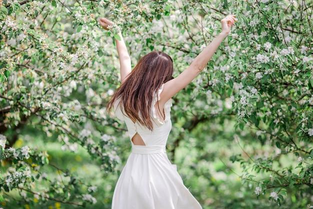 Bella donna che gode dell'odore nel giardino della ciliegia di primavera Foto Premium