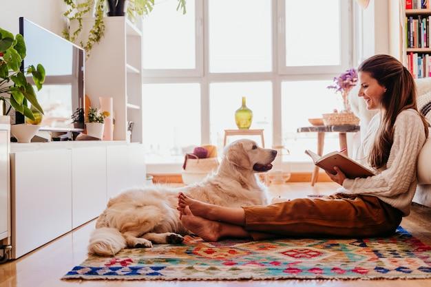 Bella donna che gode di una tazza di caffè durante la prima colazione sana a casa. scrivere su quaderno. adorabile cane golden retriever inoltre. stile di vita al chiuso Foto Premium
