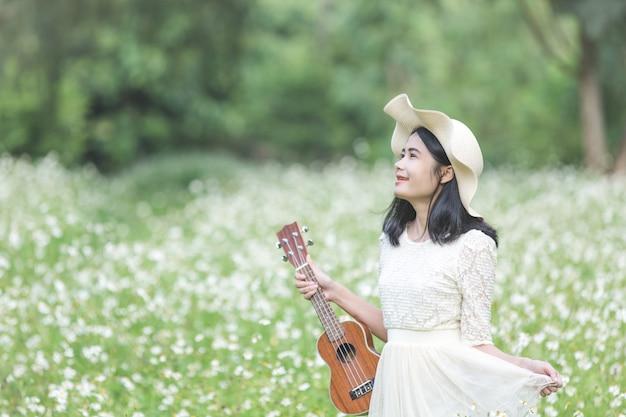 Bella donna che indossa un abito bianco carino e in possesso di un ukulele Foto Gratuite
