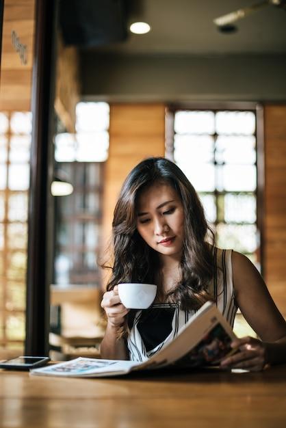 Bella donna che legge la rivista nella caffetteria Foto Gratuite