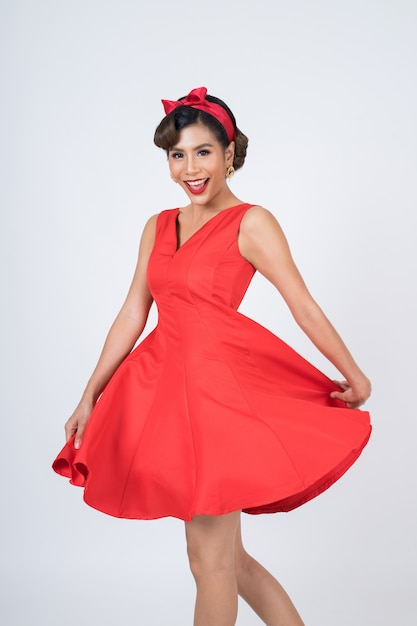 Bella donna che porta vestito rosso in studio Foto Gratuite