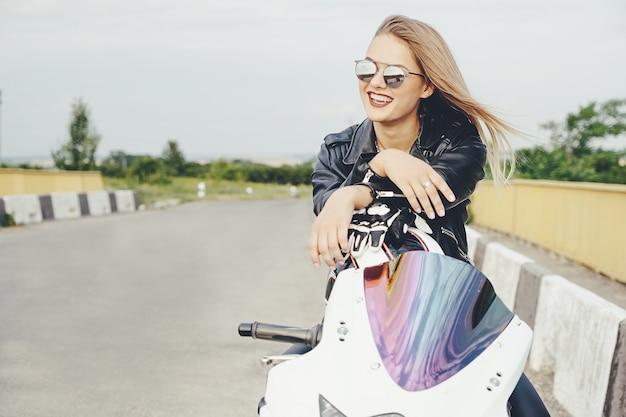 Bella donna che posa con gli occhiali da sole su una motocicletta Foto Gratuite