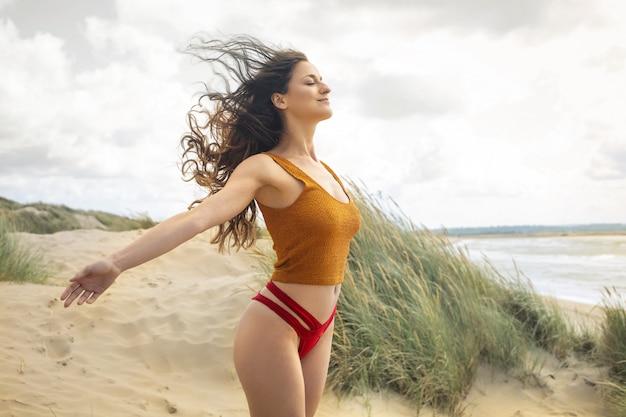 Bella donna che respira profondamente, mentre ci si rilassa in spiaggia Foto Premium