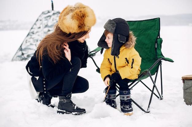 Bella donna che si siede su una pesca invernale con il figlio Foto Gratuite