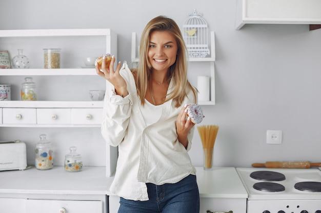 Bella donna che sta in una cucina con la ciambella Foto Gratuite