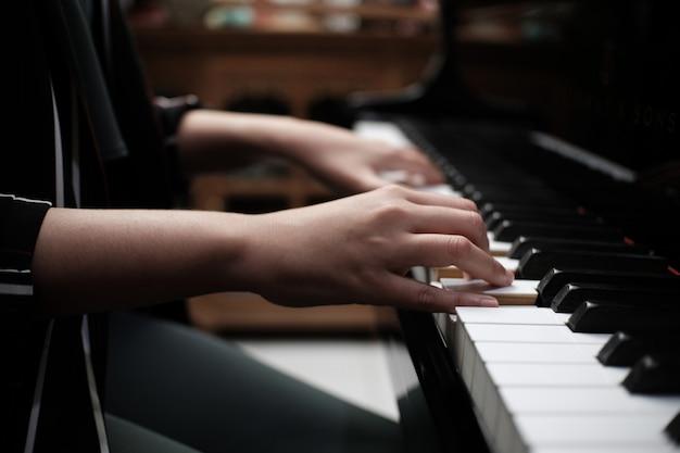 Bella donna che suona il pianoforte, impara a suonare il piano. Foto Premium