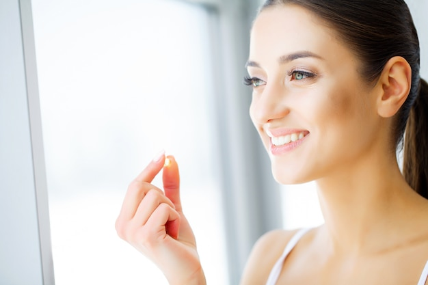 Bella donna che tiene la pillola di olio di pesce in mano. nutrizione sana Foto Premium