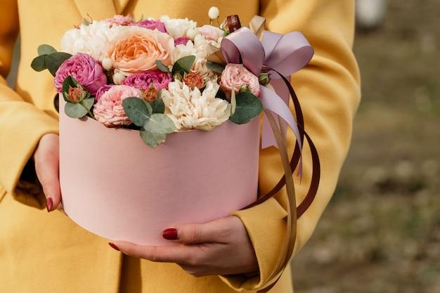 Bella donna che tiene scatola rosa con fiori. regalo per la festa della donna. Foto Premium