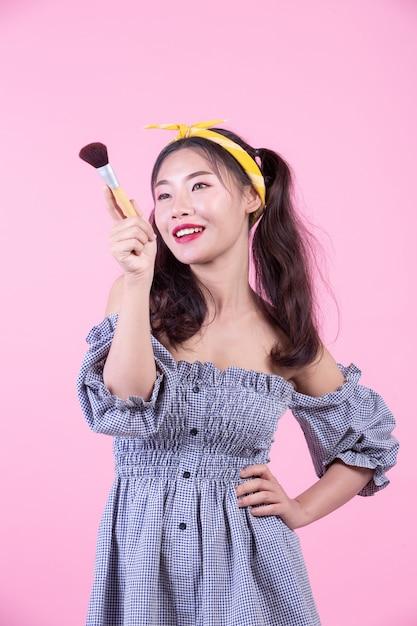 Bella donna che tiene un pennello, spazzolato su uno sfondo rosa. Foto Gratuite