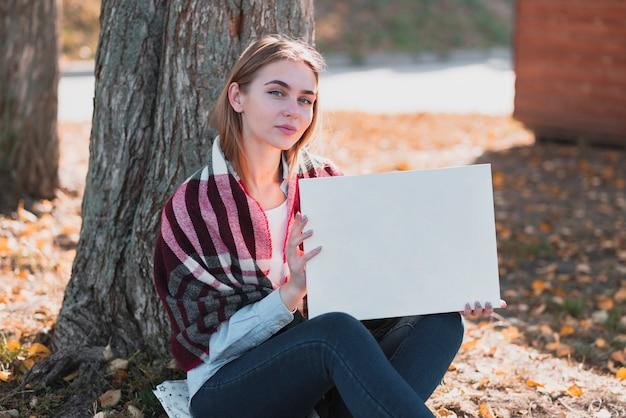 Bella donna che tiene una cornice con mockup Foto Gratuite