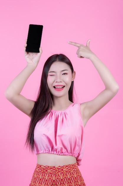 Bella donna che tiene uno smartphone su uno sfondo rosa. Foto Gratuite