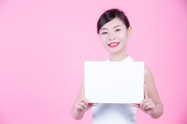 Bella donna che tiene uno strato del bordo bianco su una priorità bassa dentellare. Foto Gratuite