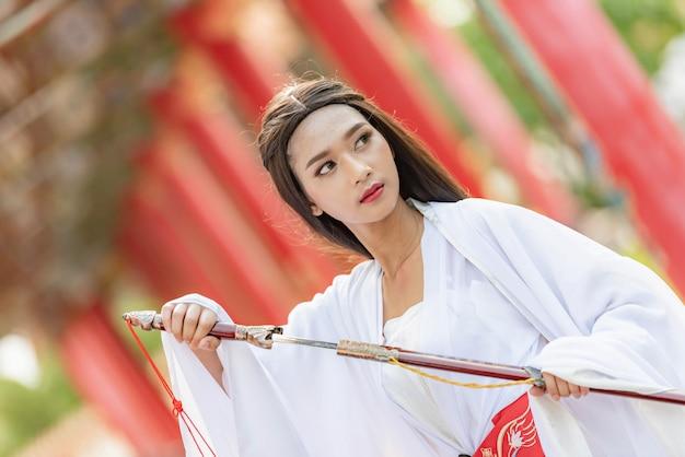 Bella donna cinese con un abito tradizionale con una spada affilata nelle sue mani. Foto Premium