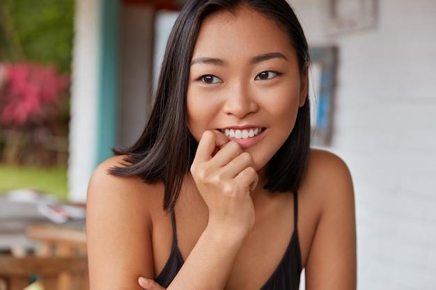 Bella donna cinese ritratto con acconciatura bobbed, pose in camera accogliente Foto Gratuite