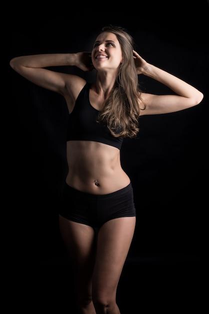 Bella donna con corpo sano su sfondo nero Foto Gratuite