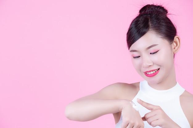 Bella donna con crema sulla pelle su uno sfondo rosa. Foto Gratuite