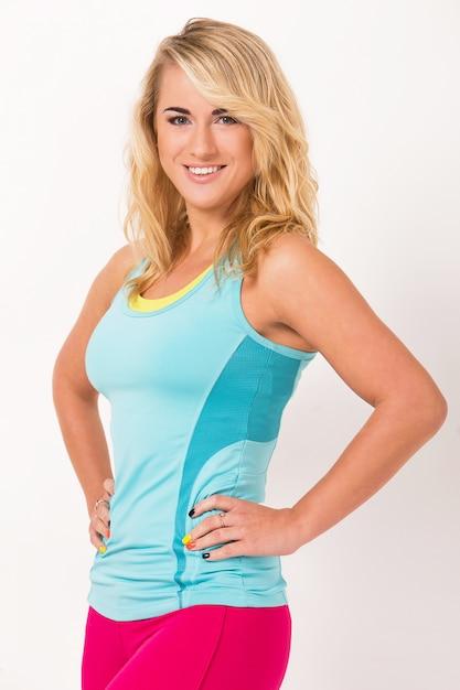 Bella donna con i capelli biondi e in abiti di allenamento sta lavorando su uno sfondo bianco Foto Gratuite