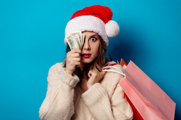 Bella donna con i sacchetti della spesa e l'orologio dei soldi sulla parete blu Foto Premium