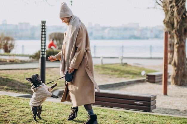 Bella donna con il bulldog francese che cammina nel parco Foto Gratuite