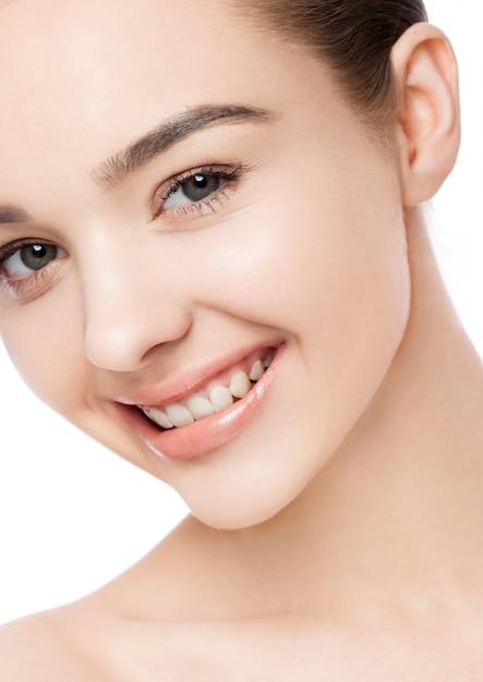 Bella donna con il ritratto naturale di cura di pelle della stazione termale di trucco di sorriso sveglio su fondo bianco Foto Premium