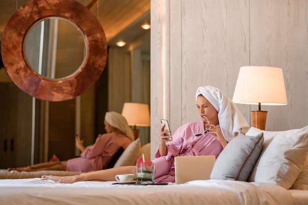 Bella donna con l'asciugamano sulla testa che parla sul telefono in camera da letto a casa. la routine mattutina. Foto Premium