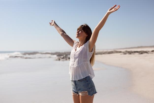 Bella donna con le braccia distese in piedi sulla spiaggia sotto il sole Foto Gratuite